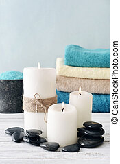 Candles with bath towels on light blue background