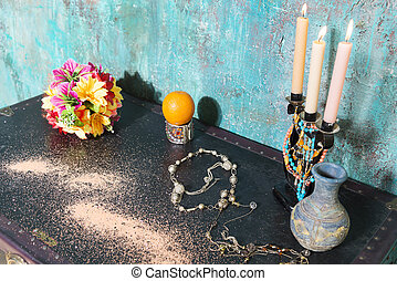Candlestick and flowers on a chest.