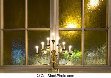 Candlestick on window ledge in church, with city lights in...