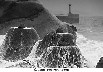 Candlestick rock formations against storm wave.