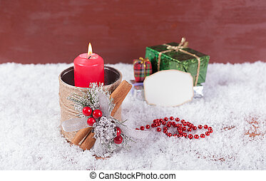 Candlestick with a red candle next to the gift box.