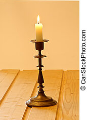 candlestick with candle on woode plate
