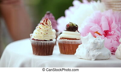 candy bar. female hands put on table cream cakes with strawberries