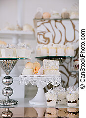 Candy bar. White wedding cake decorated by flowers standing of festive table with deserts, strawberry tartlet and cupcakes. Wedding. Reception Tartlets