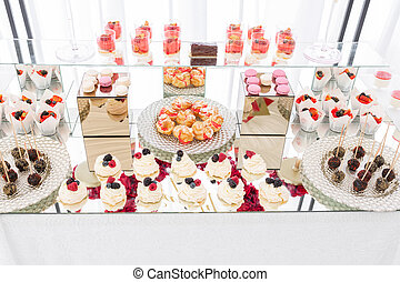 Candy bar with a lot of desserts, meringue, cupcake, fruit and sweet cakes. Sweet table for birthday or wedding.