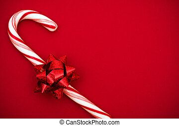 Candy Cane - Candy cane with red bow on red background,...