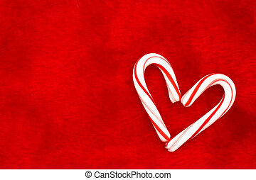 Candy Cane Heart - Two candy canes making a heart on a red...