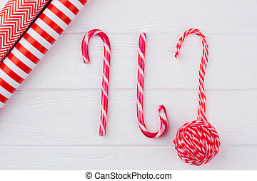 Candy canes, wrapping paper, ball of yarn.