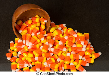 Candy corn and wooden bowl