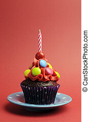 Candy covered chocolate cupcake with red frosting and candy and one birthday candle on red background for Childrens birthday party - with copy space.