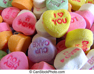 """Closeup of a bunch of little tiny candy hearts in different colors. Each heart say something different such as """"I love you, ect."""""""