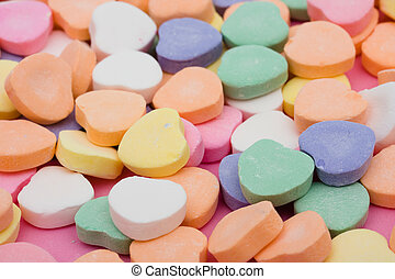 Multi color candy hearts on a pink background