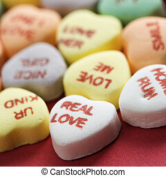 Colorful candy hearts with sayings on them arranged on red background.