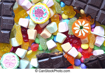 Candy, lollipop, chocolate, colored smarties and gummy bears background