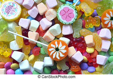Candy, lollipop, colored smarties and gummy bears background