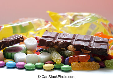Candy, lollipop, colored smarties, chocolate and gummy bears background