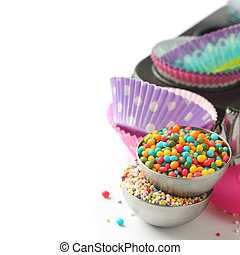 Candy sprinkles with cupcake cases and baking pan over white