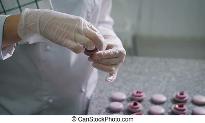 Candy store. Decoration of the French macaroons. The worker...