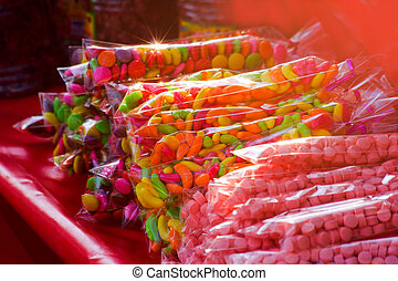 Candys buffet - Candys multi colored in plastic bag on red...