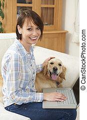 cane, seduta, accanto a, femmina, proprietario, usando computer portatile