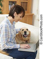 cane, seduta, accanto a, proprietario, usando computer portatile