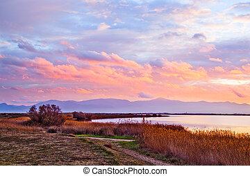 """Cloudy winter sunset at """"Etang de Canet-Saint Nazaire"""" lake near Canet plage village, Perpignan city, southern France"""