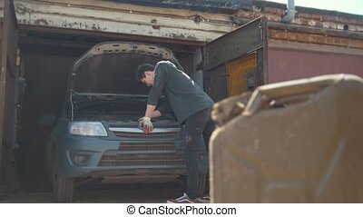 Canister stands in front of young man repairs car in garage,...