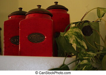 Canisters - Three red canisters and a potted plant on a...