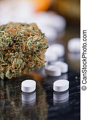 Cannabis buds and prescriptions pills over reflective...