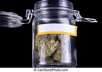 cannabis buds (maui skunk strain) on a glass jar isolated over black background