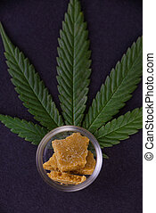 Cannabis concentrate extracted from the marijuana plant over black background
