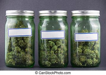 Cannabis glass jars over grey background - medical marijuana...