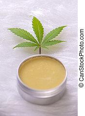 Cannabis hemp cream with marijuana leaf over white background