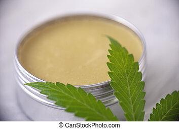 Cannabis hemp cream with marijuana leaf over white...