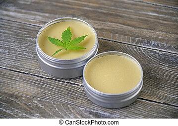 Cannabis hemp cream with marijuana leaf over wood backgroun