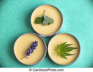 Cannabis salve made from hemp and CBD oils with mint, lavender and marijuana leaves on green background