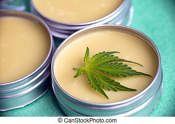 Cannabis salve with hemp and CBD oil and marijuana leaves on green background
