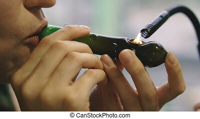 Cannabis. Smoking cannabis through a pipe