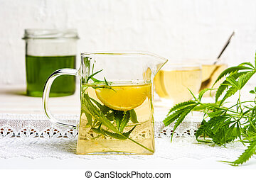 Cannabis tea with lemon and marijuana leaves