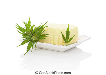 Cannabutter with marijuana leaf on saucer, isolated on white background. Cannabis butter, natural remedy.