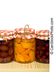 Homemade canned fruits in jars on the shelf - isolated