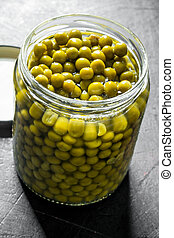 Canned green peas in a glass jar.
