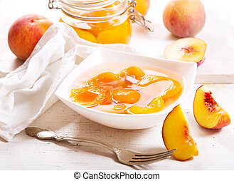 canned peaches in a bowl on wooden table