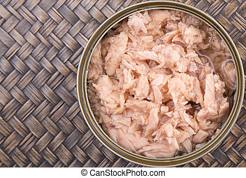 Canned Tuna - Pieces of tuna fish in a can over wicker...