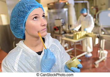 canning factory worker holding a can