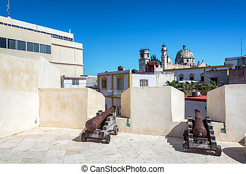 Cannons in a bastion in Campeche, Mexico with a church visible in the background