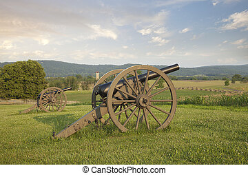 Cannon at Antietam (Sharpsburg) Battlefield in Maryland with the fence of Bloody Lane, also known as the Sunken Road in the middleground on the right.