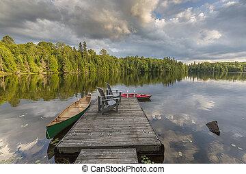 canoa, y, kayac, atado, a, un, muelle, en, un, lago, en, ontario, canadá