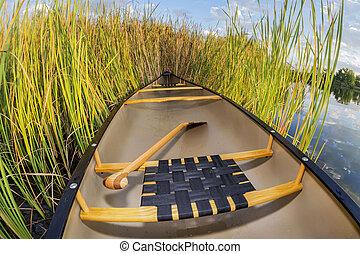 canoe and cattails - canoe on a lake shore with cattails,...