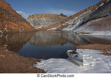 canoe and Colorado mountain lake in early spring - canoe and...